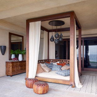 Inspiration for a tropical concrete paver back porch remodel in Orange County with a roof extension