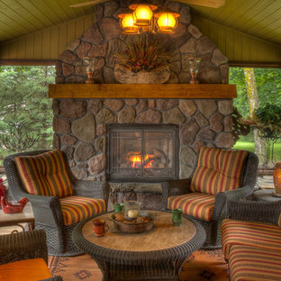 Inspiration for a rustic porch remodel in Minneapolis with a fire pit and a roof extension