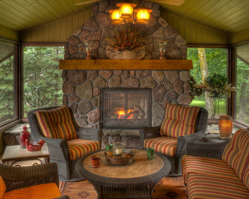 cabin with fireplace. Inspiration for a rustic porch remodel in Minneapolis with fire pit and  roof extension Cabin Fireplace Houzz