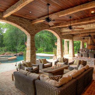 Cette photo montre un porche méditerranéen avec un foyer extérieur, des pavés en brique et une extension de toiture.