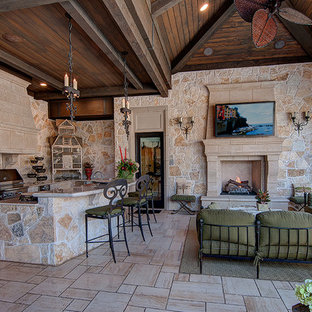 Photo of a large mediterranean back veranda in Dallas with an outdoor kitchen, tiled flooring and a roof extension.