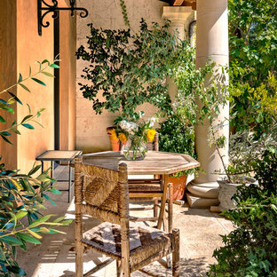This is an example of a mediterranean stone front porch design in San Francisco with an awning.