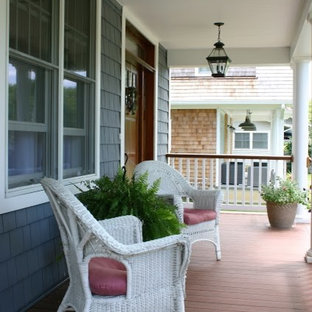 This is an example of a mid-sized traditional front porch design in New York with decking and a roof extension.