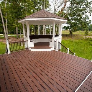 Foto di un grande portico stile americano dietro casa con pedane e un tetto a sbalzo