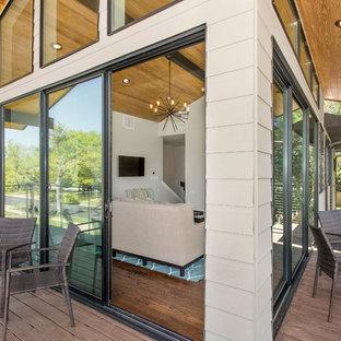 Ispirazione per un grande patio o portico moderno davanti casa con pedane e un tetto a sbalzo