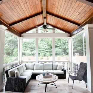 Foto di un ampio portico classico dietro casa con un portico chiuso, piastrelle e un tetto a sbalzo