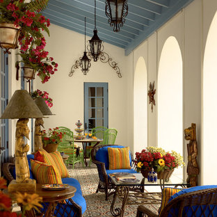 Large tuscan tile porch photo in Miami with a roof extension