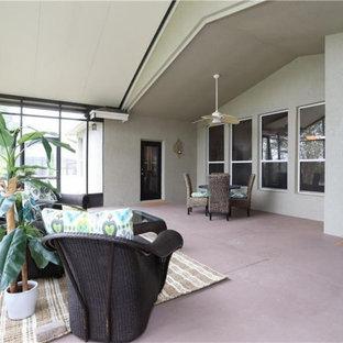 Immagine di un grande patio o portico chic dietro casa con un portico chiuso, lastre di cemento e un tetto a sbalzo