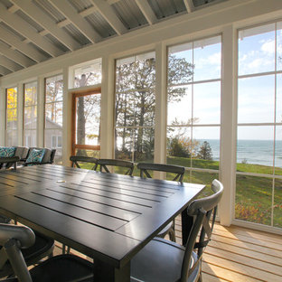 Small beach style screened-in back porch idea in Grand Rapids with decking and a roof extension