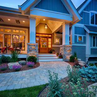 This is an example of a large craftsman front porch design in Minneapolis with decking and a roof extension.