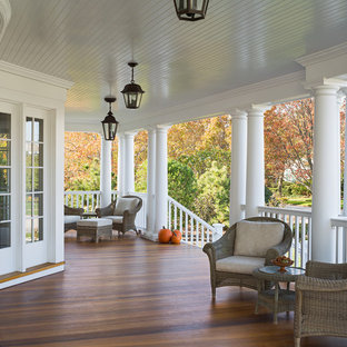 Large victorian front yard verandah in New York with decking and a roof extension.