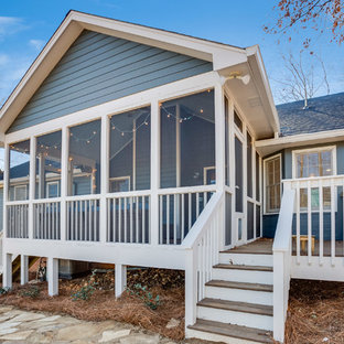 This is an example of a mid-sized transitional screened-in back porch design in Birmingham with a roof extension.