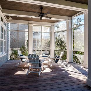 Foto di un ampio portico stile marinaro dietro casa con un portico chiuso, pedane e un tetto a sbalzo