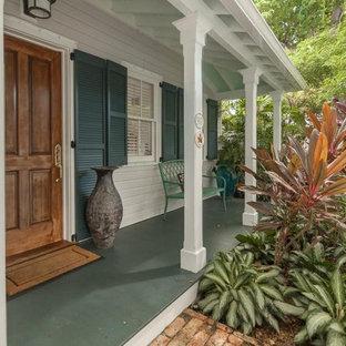 Esempio di un portico tropicale di medie dimensioni e davanti casa con pedane e un tetto a sbalzo