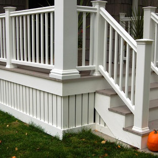 This is an example of a small traditional front porch design in Milwaukee with decking and a roof extension.