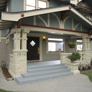 Esempio di un grande portico american style davanti casa con un tetto a sbalzo e lastre di cemento