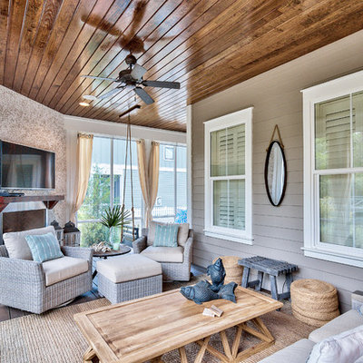 Beach style screened-in back porch photo in Miami with decking and a roof extension