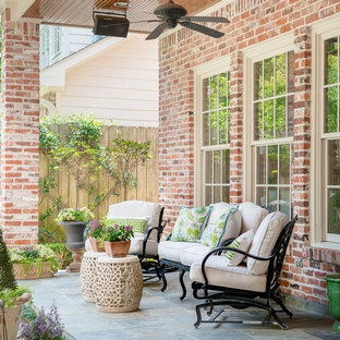 Classic porch container garden idea in Houston with a roof extension