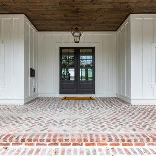 Esempio di un grande portico country davanti casa con pavimentazioni in mattoni e un tetto a sbalzo