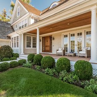 Immagine di un portico stile marino di medie dimensioni e davanti casa con un giardino in vaso, pedane e un tetto a sbalzo