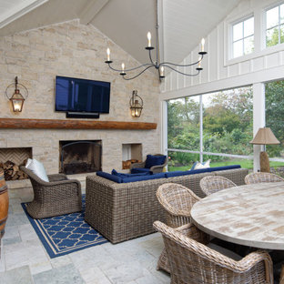 Inspiration for a large transitional stone back porch remodel in Wilmington with a fireplace and a roof extension