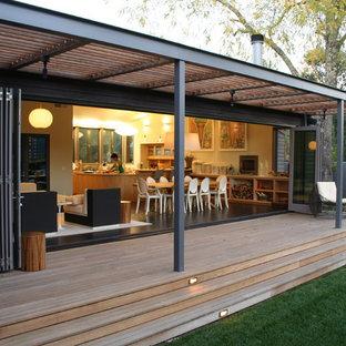 Exemple d'un grand porche arrière tendance avec une extension de toiture.