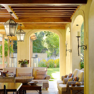 Large tuscan stone back porch idea in San Francisco with a roof extension