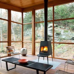 Immagine di un portico design con un focolare, pedane e un tetto a sbalzo