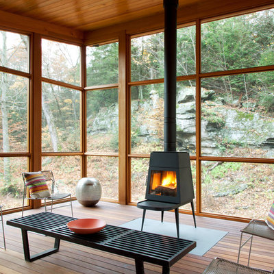 Inspiration for a contemporary porch remodel in New York with a fire pit, decking and a roof extension