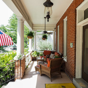 Mid-sized elegant concrete front porch photo in DC Metro with a roof extension