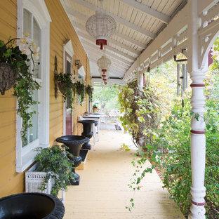 Ispirazione per un portico shabby-chic style davanti casa con pedane e un tetto a sbalzo