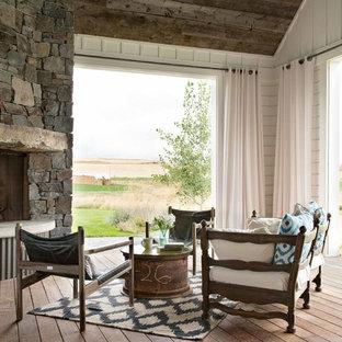 Foto på en lantlig veranda, med en öppen spis, trädäck och takförlängning