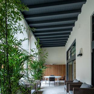 Idee per un grande patio o portico design davanti casa con un giardino in vaso, pavimentazioni in pietra naturale e un tetto a sbalzo