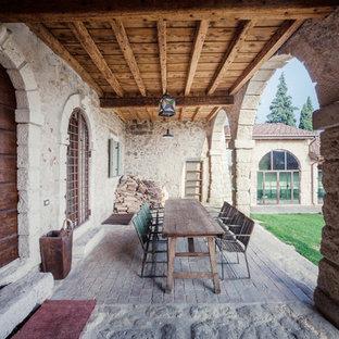 Ispirazione per un grande portico country davanti casa con pavimentazioni in pietra naturale