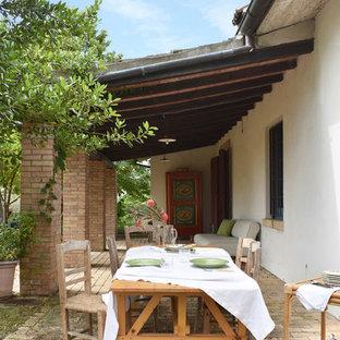 Immagine di un portico country con un tetto a sbalzo