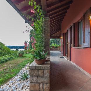 Immagine di un portico mediterraneo davanti casa con piastrelle e un tetto a sbalzo
