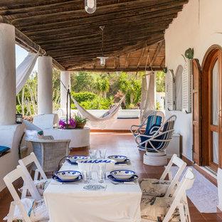 Ispirazione per un grande portico mediterraneo davanti casa con piastrelle e un tetto a sbalzo