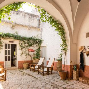 Esempio di un ampio portico mediterraneo davanti casa con un portico chiuso e pavimentazioni in pietra naturale