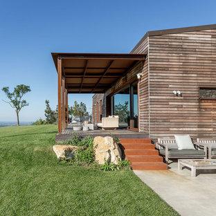 Foto di un portico country di medie dimensioni e dietro casa con pedane e un tetto a sbalzo