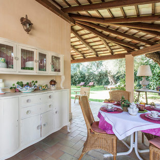 Idee per un portico mediterraneo davanti casa con pavimentazioni in mattoni, un tetto a sbalzo e con illuminazione