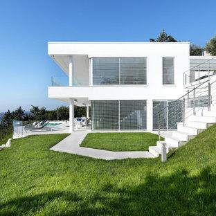 Foto di un grande portico minimal davanti casa con piastrelle e un tetto a sbalzo