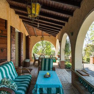 Idee per un grande portico country nel cortile laterale con un giardino in vaso, pavimentazioni in pietra naturale e un tetto a sbalzo