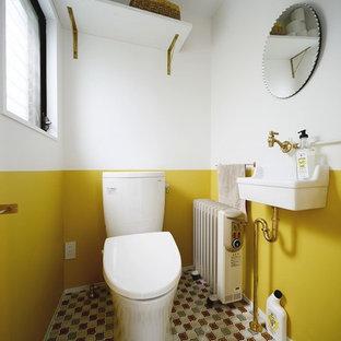 Idée de décoration pour un WC et toilettes méditerranéen avec un mur jaune, un plan vasque et un sol multicolore.