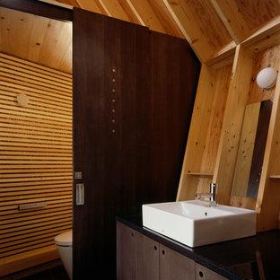 Foto de aseo asiático con armarios con paneles lisos, puertas de armario marrones, sanitario de una pieza, lavabo sobreencimera y paredes marrones
