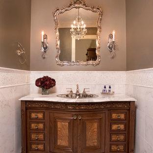 ボストンの中くらいのトラディショナルスタイルのおしゃれなトイレ・洗面所 (レイズドパネル扉のキャビネット、濃色木目調キャビネット、分離型トイレ、白いタイル、石タイル、グレーの壁、大理石の床、オーバーカウンターシンク、大理石の洗面台) の写真
