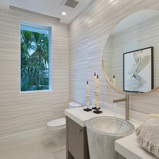 Imagen de aseo contemporáneo, de tamaño medio, con armarios con paneles lisos, paredes beige, suelo de mármol, lavabo encastrado, encimera de acrílico, suelo beige, encimeras blancas y puertas de armario grises
