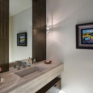 Moderne Gästetoilette mit grauer Wandfarbe, integriertem Waschbecken, Kalkstein-Waschbecken/Waschtisch und beigem Boden in Orange County