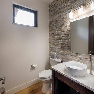 Réalisation d'un petit WC et toilettes design avec un placard en trompe-l'oeil, des portes de placard en bois sombre, un WC à poser, un carrelage gris, un carrelage de pierre, un mur gris, un sol en bois clair, une vasque, un plan de toilette en quartz et un sol marron.