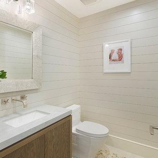 マイアミの中くらいのビーチスタイルのおしゃれなトイレ・洗面所 (フラットパネル扉のキャビネット、茶色いキャビネット、一体型トイレ、ベージュの壁、玉石タイル、アンダーカウンター洗面器、大理石の洗面台、マルチカラーの床、グレーの洗面カウンター) の写真