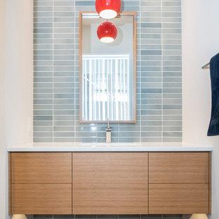 Cette image montre un WC et toilettes minimaliste avec un lavabo encastré, un placard à porte plane, des portes de placard en bois clair, un plan de toilette en quartz modifié, un carrelage bleu, des carreaux de céramique et un sol en bois foncé.